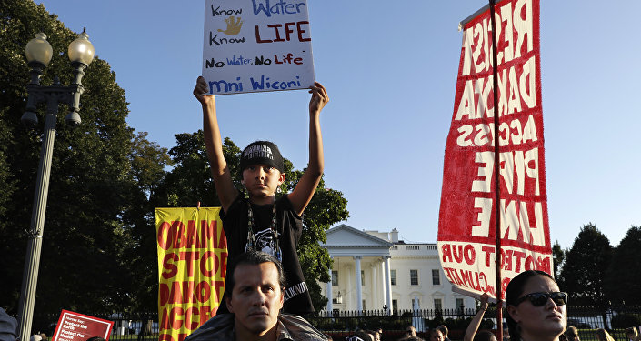 Omaka Nawicakincinji Mendoza, 7, holds a sign while on the shoulders of his father, Bill Mendoza, who is Oglala Lakota Nation and moved to Washington from Pine Ridge, S.D., as they attend a rally by the White House with members of the Standing Rock Sioux Tribe and other tribal nations and their supporters in opposition of the Dakota Access oil pipeline, Tuesday, Sept. 13, 2016, in Washington