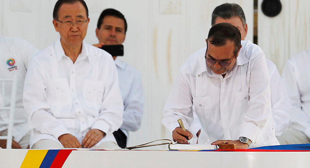 Marxist rebel leader Rodrigo Londono (R), better known by the nom de guerre Timochenko, signs an accord ending a half-century war that killed a quarter of a million people next to United Nations Secretary-General Ban Ki-moon (L), Mexican President Enrique Pena Nieto (2nd L) and Colombian President Juan Manuel Santos (partially obscured) in Cartagena, Colombia September 26, 2016.