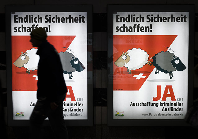 A man walks past backlit posters of the right-wing populist Swiss People's Party (SVP) that translate from German as Finally Create Security to advertise their initiative for the eviction of criminal foreigners in Zurich on February 25, 2016.