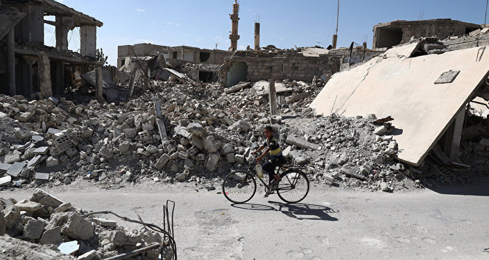 A Syrian boy rides a bicycle past destroyed buildings in the rebel-held town of Douma, on the eastern outskirts of the capital Damascus on September 25, 2016
