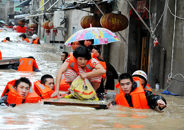 Rescuers evacuate residents through floodwaters brought by typhoon Megi in Ningde, eastern China's Fujian province on September 28, 2016