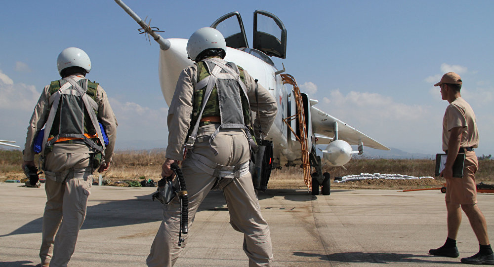 Russian pilots near a Su-24 aircraft before a mission, at the Hmeymim airbase in Syria