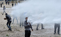 French police use water canons against participants during a march in support of migrants and refugees in the so-called 'Jungle' camp in the French northern port city of Calais on October 1, 2016.