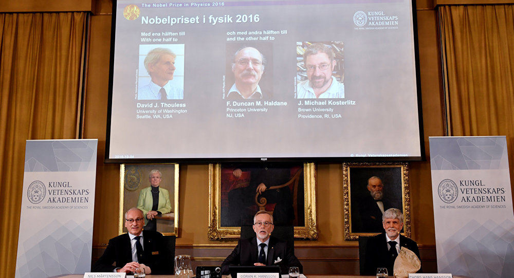 Members of the Royal Academy of Sciences, Nils Martensson (L-R), Goran K Hansson and Thomas Hans Hansson, sit under a screen showing pictures of the winners of the 2016 Nobel Prize for Physics during a news conference in Stockholm, Sweden October 4, 2016. Top from left: David Thouless, Duncan Haldane and Michael Kosterlitz.