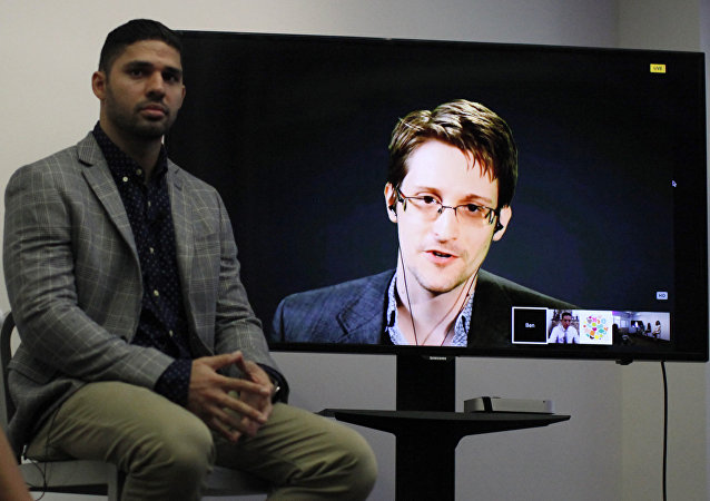 David Miranda (L) listens to American whistleblower Edward Snowden as he delivers remarks via video link from Moscow to attendees at a discussion regarding an International Treaty on the Right to Privacy, Protection Against Improper Surveillance and Protection of Whistleblowers in Manhattan in New York. (File)