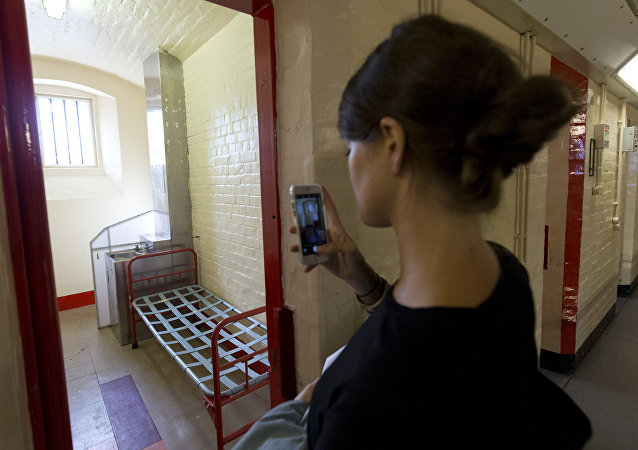 Visitors look at the prison cell of author Oscar Wilde at Reading prison during an exhibition at the prison on September 1, 2016 in Reading.