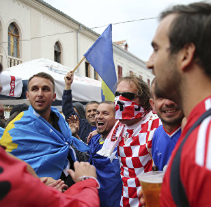 Kosovo and Croatia's fans draped in national flags sing together ahead of the World Cup Group I qualifying match between Kosovo and Croatia in main square in Shkoder, Albania on Thursday Oct. 6, 2016