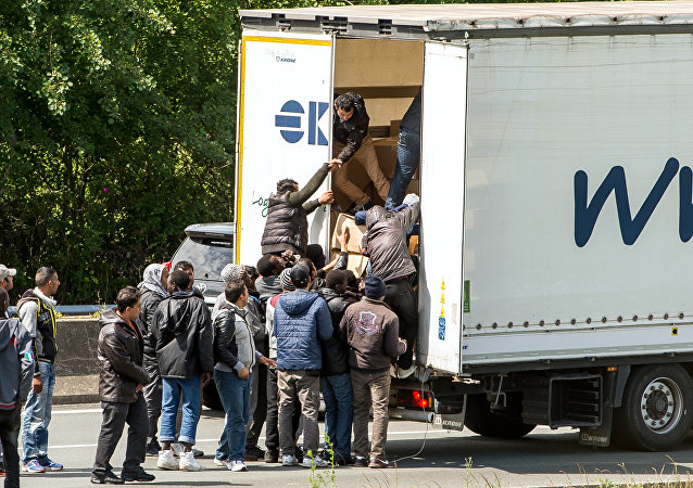 This file photo taken on June 23, 2015 shows migrants climbing in the back of a lorry on the A16 highway leading to the Eurotunnel in Calais, northern France