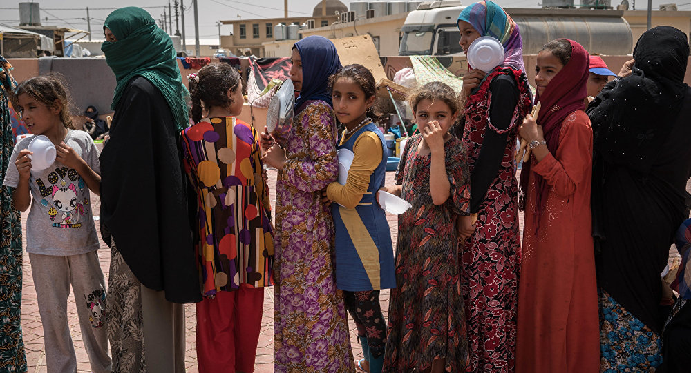 In this Aug. 7, 2016 file photo, women and children stand in line to receive a portion of food at Dibaga camp for internally displaced civilians in Iraq