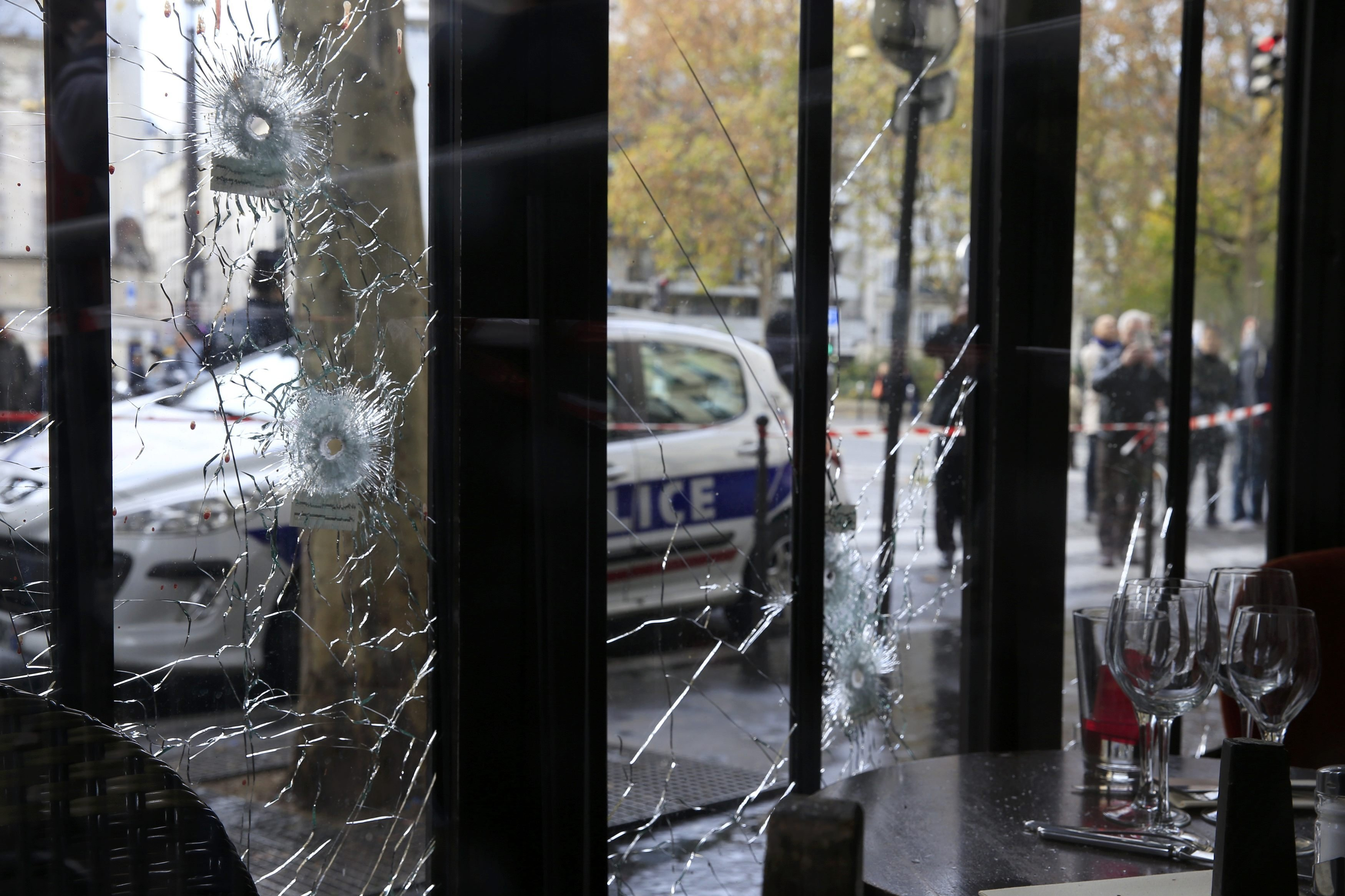 Bullet impacts are seen in the window of a restaurant window the day after a series of deadly attacks in Paris , November 14, 2015