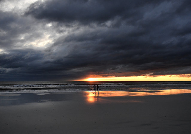 A couple watch the sunrise in Jacksonville Beach, Florida, on October 8, 2016, after Hurricane Matthew passed the area