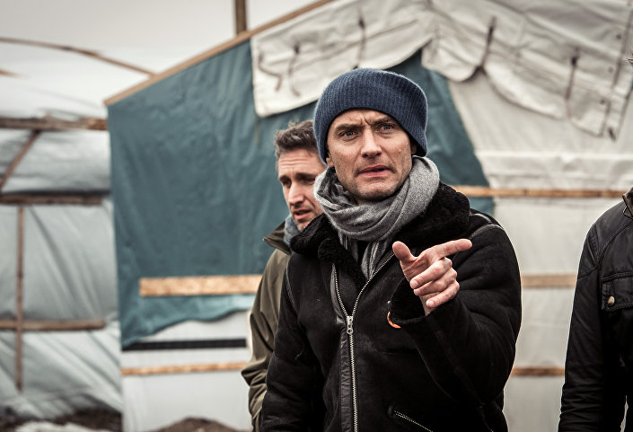British actor Jude Law gestures during a visit to the Jungle migrant camp in Calais on February 21, 2016.
