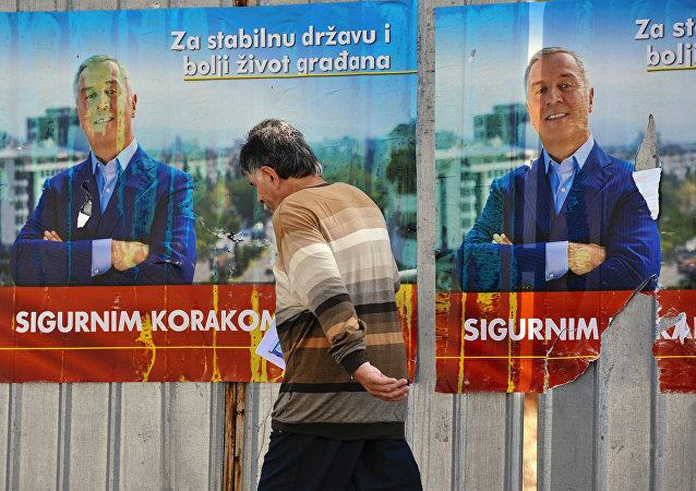 A man walks by election posters of Montenegrin Prime Minister Milo Djukanovic in Podgorica on October 14, 2016