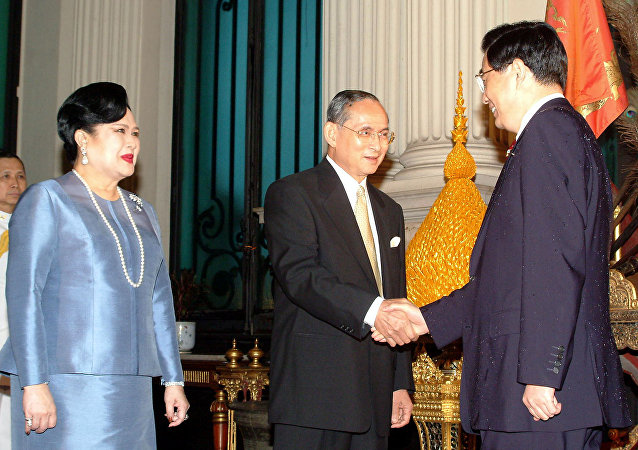 Chinese President Hu Jintao (R) shakes hands with Thai King Bhumibol Adulyadej (C) as Thai Queen Sirikit (L) looks on at the Chakri Mahaprasat Throne Hall at the Grand Palace in Bangkok, 20 October 2003