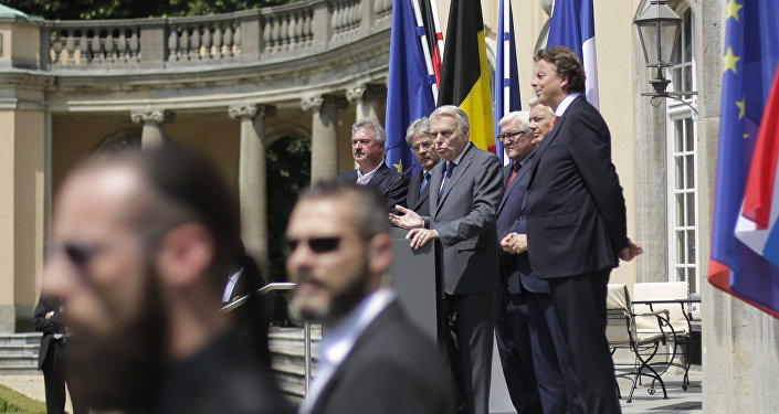 Security guards stand in front of he Foreign Ministers from EU's founding six Jean Asselborn from Luxemburg, Paolo Gentiloni from Italy, Jean-Marc Ayrault from France, Frank-Walter Steinmeier from Germany, Didier Reynders from Belgium and Bert Koenders from the Netherlands, as they brief the media after a meeting on the so-called Brexit in Berlin, Germany, Saturday, June 25, 2016