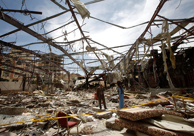 Member of the Specialized Criminal Prosecution Rajeh Zayed (L) responds to a call during a visit by human rights activists to a community hall that was struck by an air strike during a funeral on October 8, in Sanaa, Yemen, October 16, 2016