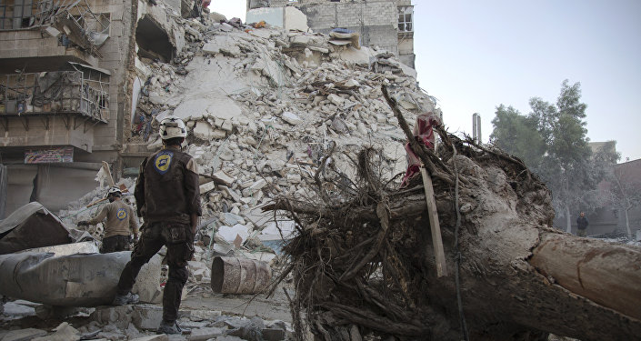 A member of the Syrian Civil Defence, known as the White Helmets, stands amid the rubble of a destroyed building during a rescue operation following reported air strikes in the rebel-held Qatarji neighbourhood of the northern city of Aleppo, on October 17, 2016