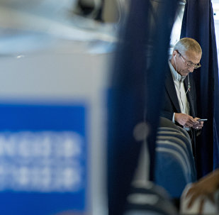 Clinton campaign manager John Podesta looks at a smartphone while aboard a plane at Westchester County Airport in White Plains, N.Y., Tuesday, Oct. 11, 2016, before traveling to Miami