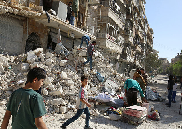 People remove belongings from a damaged site after an air strike Sunday in the rebel-held besieged al-Qaterji neighbourhood of Aleppo, Syria October 17, 2016