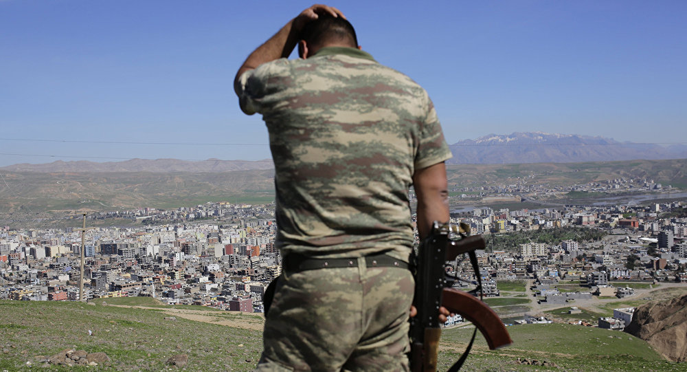 A Turkish soldier gestures while standing on the hill overlooking damaged buildings following heavy fighting between government troops and Kurdish fighters in the Kurdish town of Cizre in southeastern Turkey, which lies near the border with Syria and Iraq, on March 2, 2016