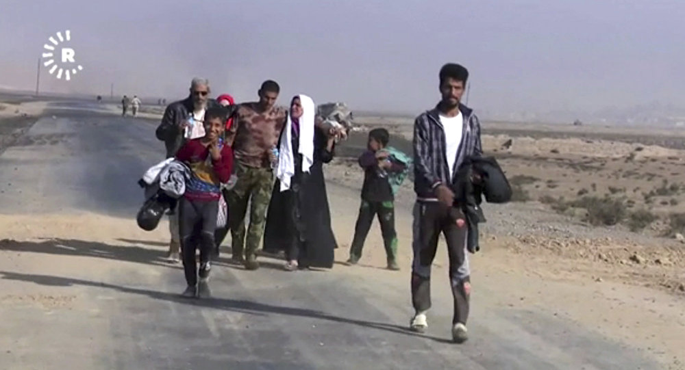 This image made from video by Rudaw News Agency shows a family fleeing Mosul, Iraq on Tuesday, Oct. 18, 2016