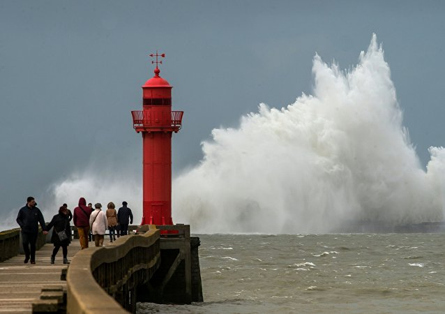 A wave breaks against a pier in front of a lighthouse in Boulogne-sur-Mer.