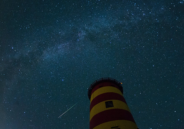 A falling star crosses the night sky behind the lighthouse in Pilsum, northwestern Germany