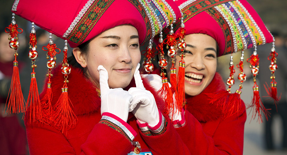 Hostesses pose for photos outside the Great Hall of the People during the opening session of the annual National People's Congress in Beijing