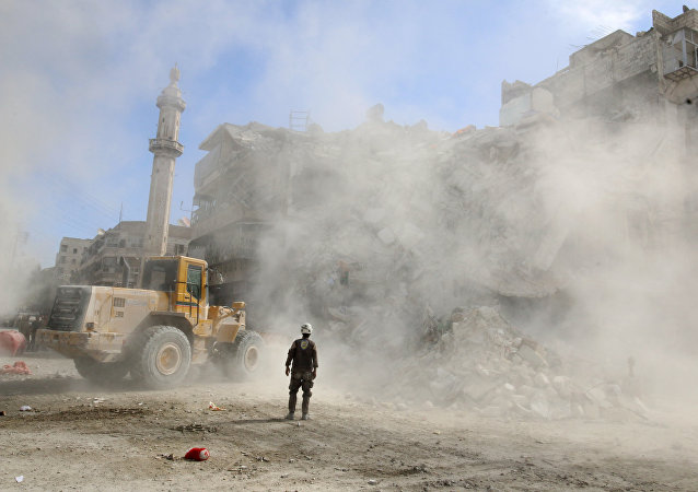 A Civil Defence member stands as a front loader removes debris after an air strike Sunday in the rebel-held besieged al-Qaterji neighbourhood of Aleppo, Syria October 17, 2016.