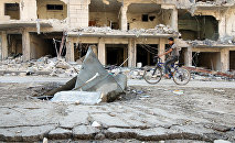 A man rides a bicycle near damaged ground in the rebel held besieged al-Sukkari neighbourhood of Aleppo, Syria October 19, 2016.