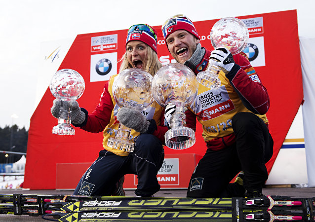 Norway's Therese Johaug (L) and Norway's Martin Johnsrud Sundby pose with their overall World Cup trophies during the winners presentation at the FIS Cross-Country World Cup on March 16, 2014 in Falun
