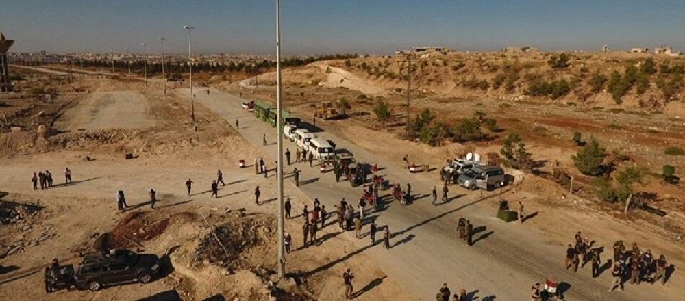 Law enforcement officers near cars and ambulances in a humanitarian corridor for civilians and militants along the Castello Road in northern Aleppo, Syria