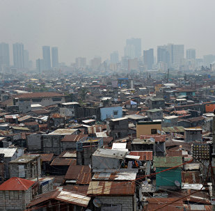 This general view shows informal settlers' homes (foreground) dwarped by highrise buildings in the background near the port of Manila