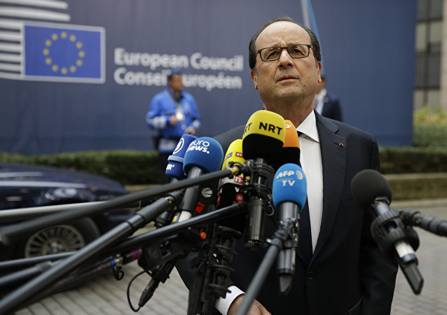French President Francois Hollande speaks to media reporters as he arrives for the EU summit in Brussels.