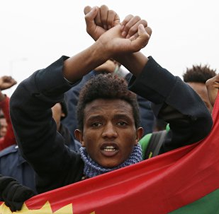 Ethiopian migrants, members of the Oromo community, react as they leave the Jungle to be transfered to reception centers during the start of the dismantlement of the camp in Calais, France, October 24, 2016.