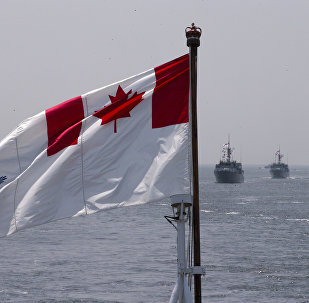 The Royal Canadian Navy Ensign flies on the HMCS Kingston and HMCS Moncton sail behind during the Parade of Ships entering the New York Harbor, Wednesday, May 25, 2016