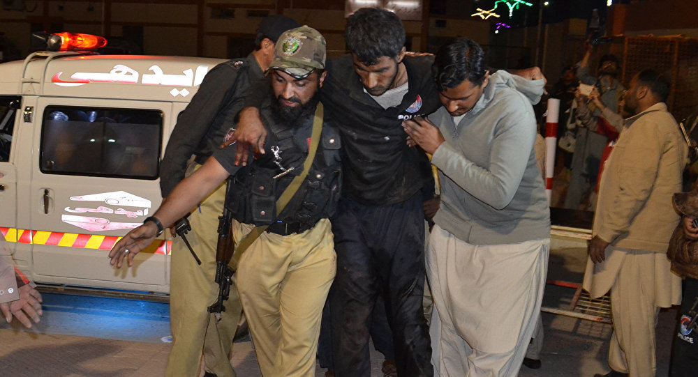 A Pakistani volunteer and a police officer rush an injured person to a hospital in Quetta, Pakistan, Monday, Oct. 24, 2016, after two separate attacks in Pakistan