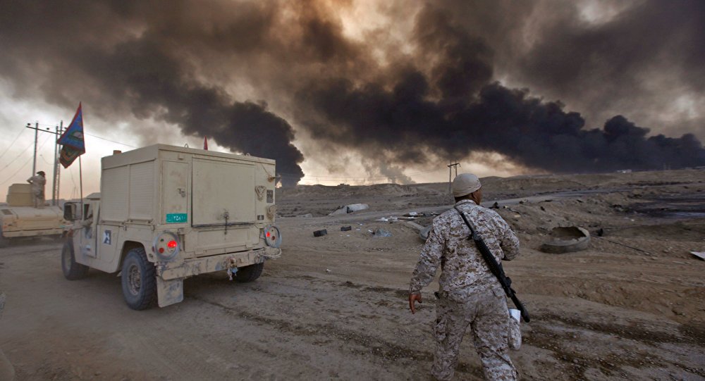 Iraqi army are seen in Qayyara, Iraq, October 22, 2016. The fumes in the background are from oil wells that were set ablaze by Islamic State militants