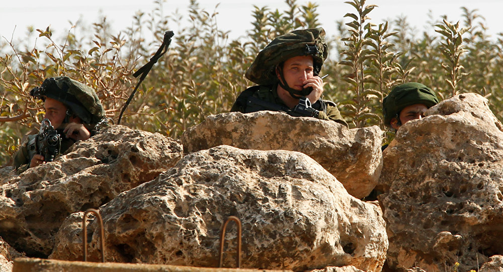 Israeli soldiers take position in the Israeli town of Metulla, as seen from the border village of Kfar Kila, south Lebanon October 26, 2016