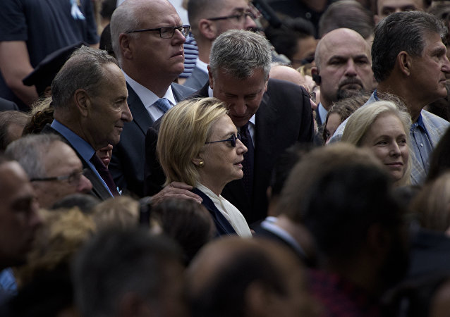 New York City Mayor Bill de Blasio speaks to US Democratic presidential nominee Hillary Clinton during a memorial service at the National 9/11 Memorial September 11, 2016 in New York
