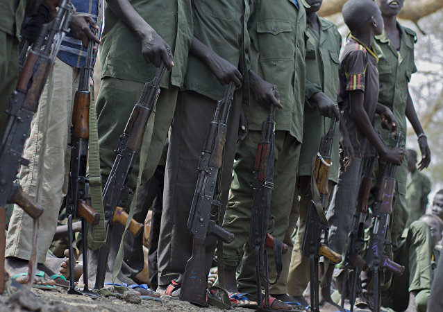 Young boys, children soldiers sit on February 10, 2015 prepare to lay down their arms at a ceremony of the child soldiers disarmament, demobilisation and reintegration in Pibor oversawn by UNICEF and partners