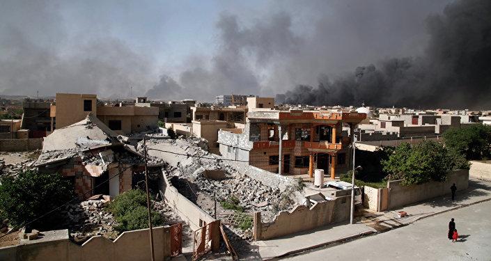 People walk along a street as smoke rises near Qayyarah, south of Mosul, Iraq