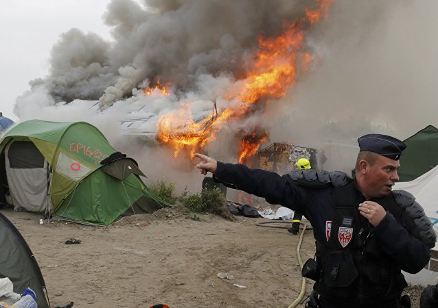 French CRS riot police secure the area near burning makeshift shelters and tents in the Jungle on the third day of the evacuation of migrants and their transfer to reception centers in France, as part of the dismantlement of the camp in Calais, France, October 26, 2016.
