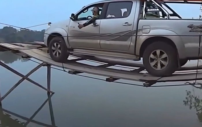 Risky travel by car over the bridge across the river