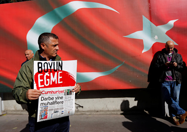A supporter of Cumhuriyet newspaper, an opposition secularist daily, holds a placard and the latest copy during a protest in front of its headquarters in Istanbul, Turkey, October 31, 2016. The placard reads, Don't bow down.