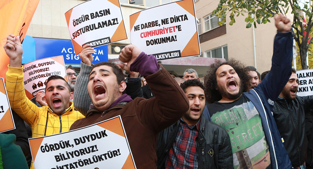 Participants hold placards reading 'Free press can't be silenced' (C) and 'Do not touch Cumhuriyet' (R) outside the headquarters of Turkish newspaper Cumhuriyet in Ankara on October 31, 2016, during a protest against the detention of the newspaper's editor-in-chief and a dozen journalists and executives