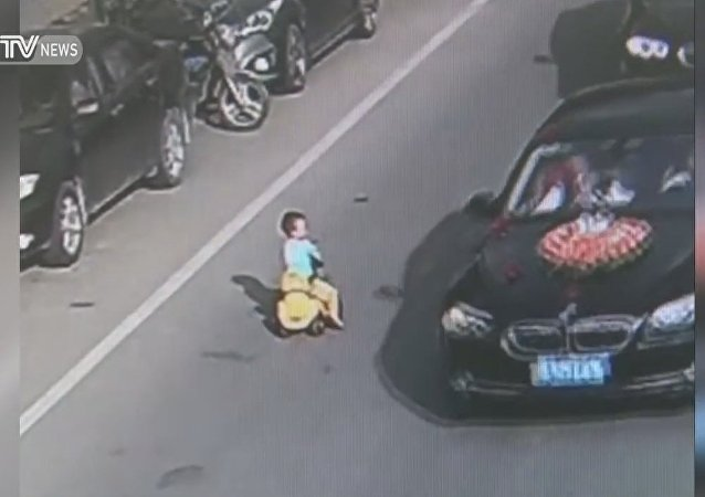 Kid drives toy car through traffic on busy road