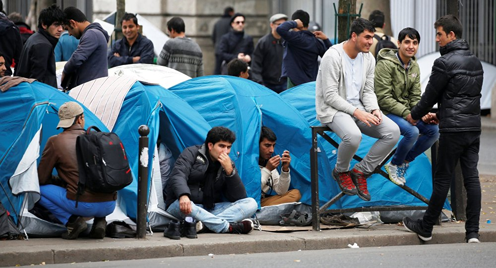Migrants sit in their tents at a makeshift migrant camp on a street near the metro stations of Jaures and Stalingrad in Paris, France, October 28, 2016.