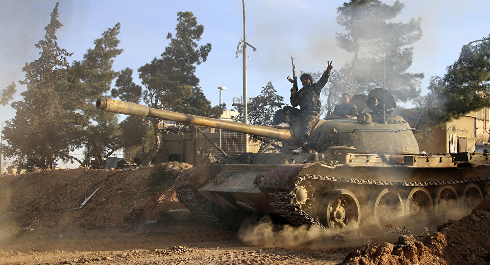 Volunteer fighter with the Syrian Government forces sits atop a tank in the province of Raqqa, Syria (File)