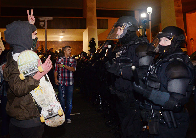 A protestor gestures at police at Pioneer Square in Portland, Oregon on November 11, 2016, to protest the election of US President-elect Donald Trump.
